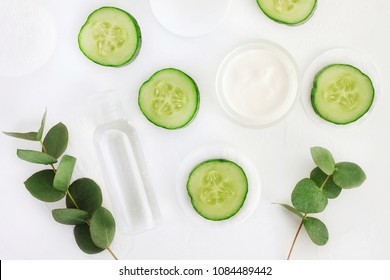 Fresh cucumber slices, cosmetic moisturizer, facial tonic, top view white background. Natural skincare, white and green colors.