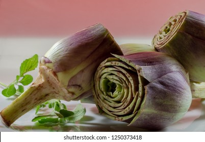 fresh cut artichokes composition on white and pink color background