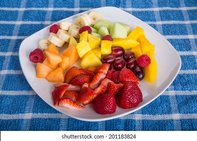 Fresh cut fruit on a white plate with strawberries, mango, pineapple, grapes, bananas, and melon