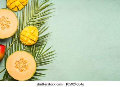 fresh cut melon and mango laid on tropical leaves on a blue rustic background, space for text, top view flat lay