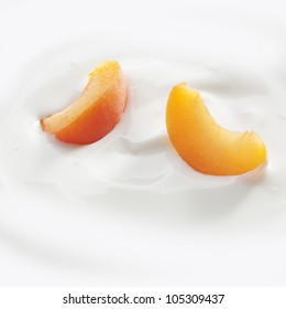 Fresh cut peach slices lay lightly on a fresh serving of yogurt