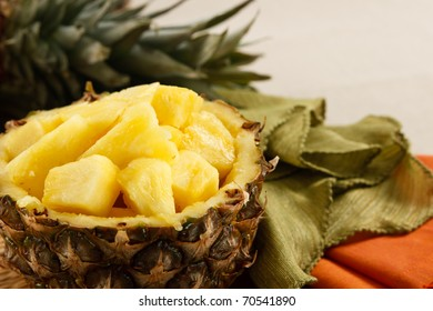 Fresh cut pineapple served in a natural bowl, set against colorful napkins on a beige linen tablecloth.