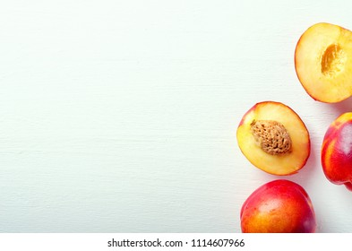 Fresh cut and whole ripe nectarines on a white background. Healthy food. Copy space.