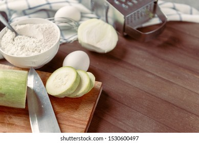 fresh cut zucchini on a Board, knife, plate with flour, eggs, onion, grater, towel on a wooden background,  copy space