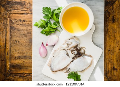 Fresh cuttlefish and ingredients for preparing cooking sauce for rice or pasta with squids or cuttlefish, parsley and broth.