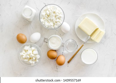 Fresh dairy products for breakfast with milk, cottage, eggs, butter, yougurt on white marble background top view mock up