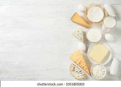 Fresh dairy products and eggs on wooden background
