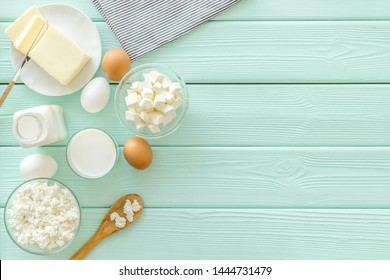 Fresh dairy products with milk, cottage, eggs, butter, yougurt on mint green wooden background top view mock up