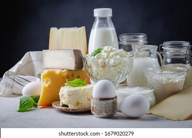Fresh dairy products, milk, cottage cheese, eggs, yogurt, sour cream and butter on white table, black background