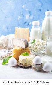 Fresh dairy products, milk, cottage cheese, eggs, yogurt, sour cream and butter on blue background