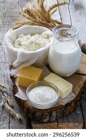 Fresh dairy products (milk, cottage cheese, cheese, sour cream, butter), wheat, rustic wood background