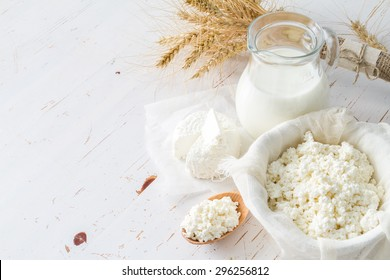 Fresh dairy products (milk, cottage cheese), wheat, white wood background, top view