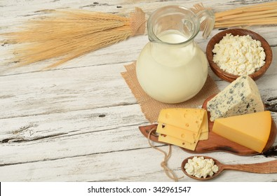 Fresh dairy products (milk, cottage cheese,cheese ), wheat, white wood background, top view. Concept of Judaic holiday Shavuot.