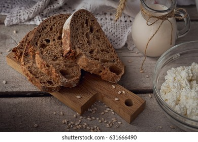 Fresh dairy products: milk, cottage cheese, sour cream, multigrain homemade bread and wheat on rustic wooden background. Organic farming dairy concept.