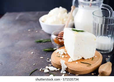 Fresh dairy products with rosemary and honey on a dark stone background,