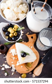 Fresh dairy products with rosemary and honey, green and black olives on a dark stone background,