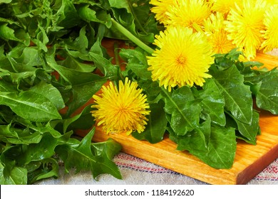 Fresh dandelion leaves with flowers on cutting board on table with linen textile, closeup, copy space. Raw organic diet concept