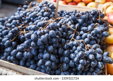 Fresh dark blue grapes in basket ready for sale at farmers marketplace