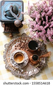 Fresh dark coffee in antique china cup, silver spoon, saucer, coffee beans, old cooper mug, cezva on round aged, weathered silver-plate tray, authentic grinder, heather, vintage style, daylight
