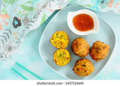 Fresh deep fried vegetable pakora with sweet chili dipping sauce.  Traditional Indian snack with a hot and spicy flavour.  In horizontal format and shot from above in flat lay composition.