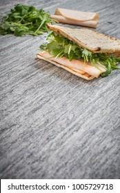 A fresh deli sandwich with lettuce and cold cuts on a granite countertop.