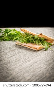 A fresh deli sandwich and lettuce on a granite counter with a black background.