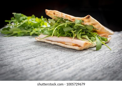 A fresh deli sandwich on a granite counter against a black background.