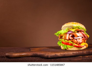 Fresh delicious big burger with bacon, tomato, cheese, cucumber, onion and lettuce on wooden background with copy space