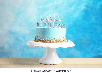 Fresh delicious birthday cake with candles on stand against color background