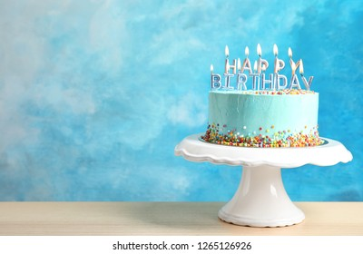Fresh delicious birthday cake with candles on stand against color background. Space for text