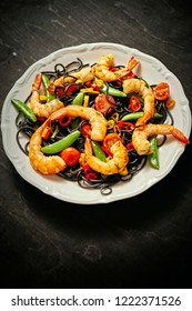 fresh, delicious black spaghetti with grilled shrimps, tomatoes, chilli peppers, on a white plate