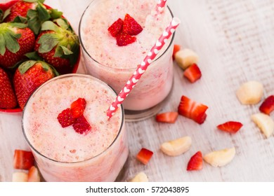 Fresh delicious breakfast smoothie with strawberries and bananas and heart straws