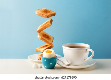 Fresh delicious breakfast with soft boiled egg, crispy toasts and cup coffee or tea on blue background. Levitation food concept. Vintage retro style