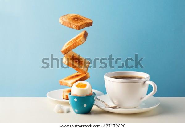 青の背景に、柔らかいゆで卵、カップコーヒー、茶を入れた新鮮でおいしい朝食。浮揚食のコンセプト。ビンテージレトロなスタイル