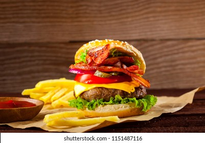 Fresh delicious burger with beef, bacon, tomato, cheese, cucumber, onion and lettuce on wooden background with copy space