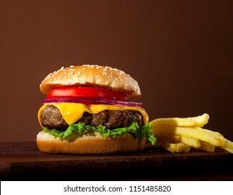 Fresh delicious burger with beef, tomato, cheese, onion and lettuce on wooden table and brown background with copy space