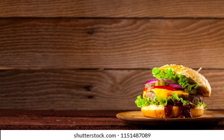 Fresh delicious burger with beef, tomato, cheese, cucumber, onion and lettuce on wooden background with copy space