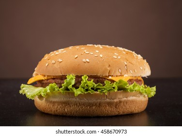 Fresh delicious burger with cheese, onion and lettuce on brown background with copy space