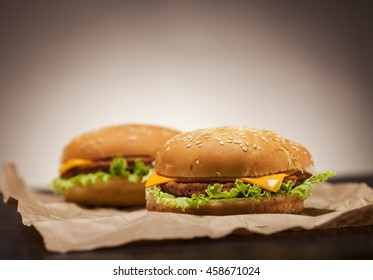 Fresh delicious burgers with cheese, onion and lettuce on brown paper and black background