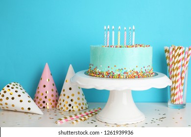 Fresh delicious cake and birthday caps on table against color background. Space for text