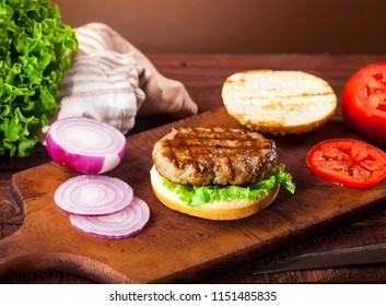 Fresh delicious cheeseburger ingredients on wooden background.