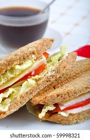 fresh and delicious classic club sandwich over a white glass dish with coffee