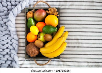 Fresh delicious fruits in a wooden box on the bed. Summer healthy raw vegan clean eating breakfast concept. Close up, top view, copy space.