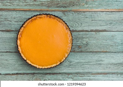 Fresh delicious homemade pumpkin pie on wooden background, top view.