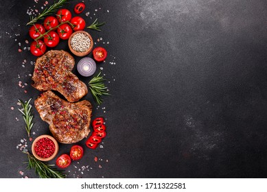 Fresh delicious juicy steak on the bones with vegetables and spices against a dark background. Pork juicy steak grill on dark table