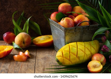 fresh and delicious peach and mango in metal basket. Ingredients for a tropical fruit smoothie with mango and citrus