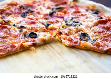 Fresh delicious Pepperoni Pizza slice cheese crust delicious tasty Italian traditional fast food served on wooden board table classic with copy space.