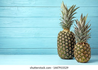 Fresh delicious pineapples on table against wooden background, space for text