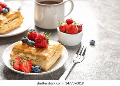 Fresh delicious puff pastry with sweet berries on grey marble table. Space for text