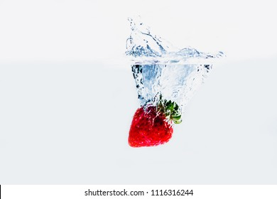 A fresh and delicious red strawberry isolated on a white background. Red strawberry dropping in water and creating a splash. The concept of healthy eating, consuming fruit.
